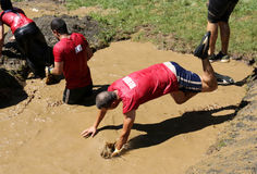 Extreme sport challenge jump in water. Sofia, Bulgaria - July 9, 2016: Participants are jumping into muddy water at the Legion Run extreme sport challenge near Royalty Free Stock Photos