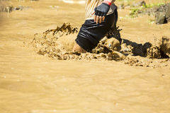 Extreme sport challenge muddy water. A participant is jumping into muddy water at an extreme sport challenge near Sofia. The sports event is mud and obstacle Stock Images