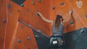 Extreme sport Een jonge vrouw die omhoog op een rotsachtige muur binnen beklimmen stock videobeelden