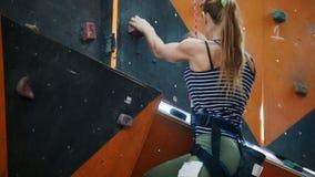 Extreme sport Een jonge vrouw probeert hard om op een rotsachtige muur binnen te beklimmen stock videobeelden