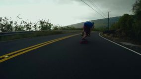 Extreme sport male skater skating downhill fast long road performing stunts on longboard in majestic 4k first person pov stock footage