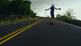 Extreme sport male skater skating downhill fast long road performing stunts on longboard in stunning 4k first person pov stock footage