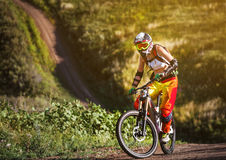 Extreme sports - young woman riding downhill bike Stock Photography