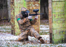 Extreme sportsman playing paintball game on first snow. In paintball club Stock Photography