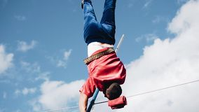 Extreme stands on his head on a cable stretched above the ground. Nice close-up. Extreme stock video footage