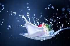 Extreme Strawberry splash. Strawberry splashing on a spoon of milk Royalty Free Stock Image