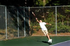 Extreme Stretch with Success. Young male tennis player does an extreme stretch and succeeds with returning the tennis ball.  He has on white shirt and tan shorts Royalty Free Stock Image