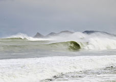 Extreme Surf Area. Big waves breaking in the coast, with some mountains in the background Stock Photos