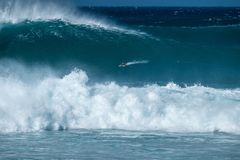 Extreme surfer. Paddles and going to ride the gigantic ocean wave of the Banzai Pipeline surf spot. The North Shore of Oahu, Hawaii stock photo