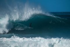 Extreme surfer. Rides gigantic ocean wave of the Banzai Pipeline surf spot. The North Shore of Oahu, Hawaii stock image