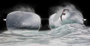 Extreme Surfer Short Board. Waves and sea spray crashing through lenses of sunglasses with a surfer riding short board executing arial maneuver, a concept for royalty free stock image