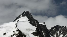 Grossglockner peak north side zoom in. Extreme telephoto shot zooming in on the Grossglockner, highest mountain in Austria, as seen from the north side, together stock video footage