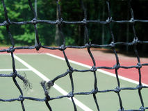 Extreme tennis. Close-up view of a broken tennis net - lines of the court shown in background Stock Photography