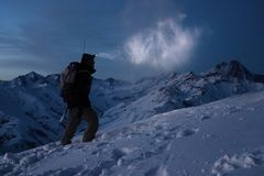 Extreme tourism. Brave expeditor lights the way with a headlamp at night winter mountains. Man with backpack commit climb on snowy. Slope in high ridge. Ski Royalty Free Stock Photography