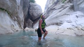 Extreme tourism, happy active tourist girl into protective helmet and clothes with pleasure exploring beautiful area. In cave with water on background of huge stock video