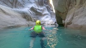 Extreme travel, active lifestyle holiday of woman in extreme conditions is swimming in protective clothing between huge. Extreme travel, active lifestyle holiday stock video