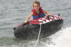 Extreme tubing. A little boy tubing behind a boat at the lake royalty free stock photos
