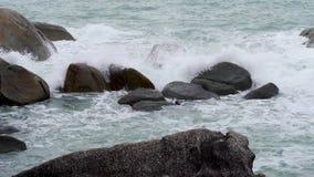 Extreme wave crashing rocks on sea coast