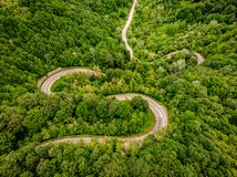 Extreme winding highway in the forest. Aerial image shot using a drone stock photos
