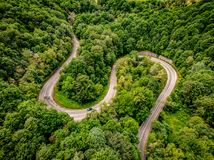 Extreme winding highway in the mountains passing trough a forest. Aerial view stock photos