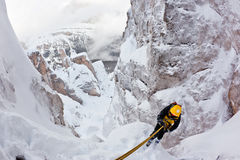 Extreme winter mountaineering. Climber abseiling back down using a double rope during an extreme winter climbing. Dolomiti (East Alps), Trentino, Italy, Europe stock photo