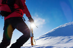 Extreme winter sports: climber at the top of a snowy peak in the Royalty Free Stock Image