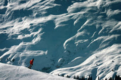 Extreme Wintersport - Scale Differences. A human figure snowboarding in the Swiss alps. Scale difference between massive mountains and humans become apparent Royalty Free Stock Photos
