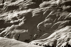 Extreme Wintersport - Scale Differences. A human figure snowboarding in the Swiss alps. Scale difference between massive mountains and humans become apparent Royalty Free Stock Images