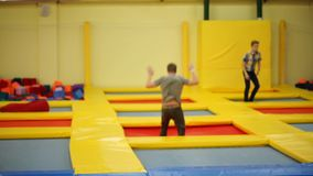 Single acrobat is doing series of jumps on a trampoline in a sport hall stock video footage