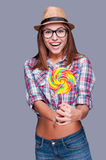 Extremely big lollipop. Surprised young woman in funky hat holding a big lollipop and keeping mouth open while standing against grey background Royalty Free Stock Photos