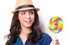 Extremely big lollipop. Young beautiful woman in funky looking at big lollipop and keeping mouth open while standing against white background Royalty Free Stock Images