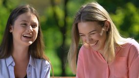 Extremely cheerful female friends laughing during rest in summer park, relations
