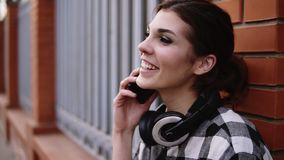 Extremely close footage. Stunning, young girl is talking on mobile phone with friend. Standing outside leaning on a. Brick fence. Trendy. Happy. Headphones on stock video