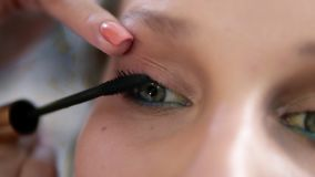 Extremely close of a young woman`s eye. Make up artist carefully applying a black mascara. Caucasian model with green stock video footage