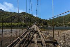 Extremely dilapidated suspension bridge only provisionally repaired, dangerous bridge in Albania, Balkan stock photo