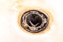 Extremely dirty bath drain mesh, hole covered with limescale or lime scale and rust close up, cleaning calcified and rusty. Bathroom equipment concept royalty free stock photography