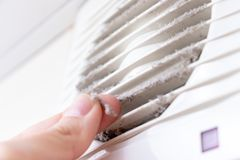Extremely dirty and dusty white plastic ventilation air grille at home close up and a hand holding dust by fingers, harmful for royalty free stock photography