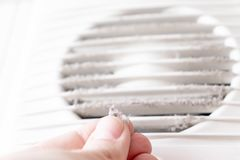Extremely dirty and dusty white plastic ventilation air grille at home close up and a hand holding dust by fingers, harmful for stock photo