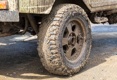 Extremely dirty SUV wheel after driving in the rain. On dirty rural road Royalty Free Stock Image