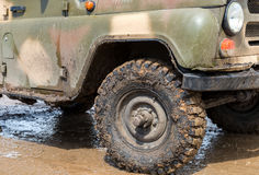 Extremely dirty SUV wheel after driving in the rain. On dirty rural road Stock Photos