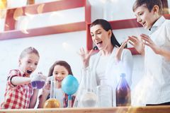 Extremely excited children and teacher mixing liquids during chemistry lesson. Having fun together. Very emotional group of pupils standing next to their teacher Royalty Free Stock Photography