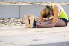 Extremely flexible woman. Young, very flexible woman in sportswear, touching her knees with her nose. She's stretching her muscles during a training run on the Stock Images