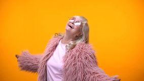 Extremely happy aged woman in pink coat looking up, enjoying life, having fun royalty free stock photo