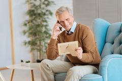 Extremely happy elderly man talking with family on phone. Miss you so much. Loving senior man smiling cheerfully while looking at a family photo and talking with Royalty Free Stock Images
