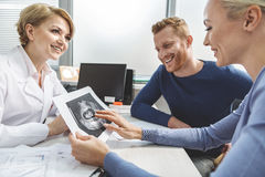 Extremely happy future parents coming to doctor stock photos