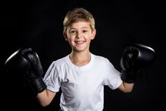 Extremely happy little boxer fighter portrait in black boxing gloves with hands up. The little winner.  Stock Images