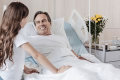 Extremely happy man smiling while looking at daughter in hospital. I believe in you daddy. Selective focus on a radiant gentleman lying in a hospital bed and Royalty Free Stock Image