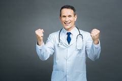 Extremely happy medical professional showing winning sigh. Hurray. Waist up shot of an excited male doctor grinning broadly while looking into the camera and Stock Images