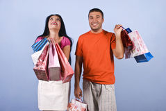 Extremely happy woman at shopping. Yes!I did it!Bought what i wanted!Shopaholic woman it is extremely happy and laughing and the guy smiling and looking  doubt Royalty Free Stock Images