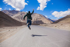 Extremely happy young male tourist jumping on country road with giant mountains behind Royalty Free Stock Photos
